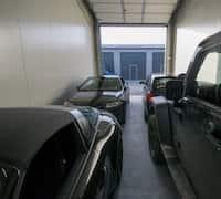 Innenansicht einer Lagerhalle mit vier PKWs.